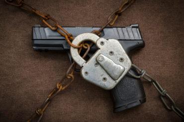 A gun behind chains with a padlock.
